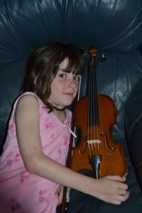 Miss cuddling her new violin. I'd found someone selling two Stentor II violins on Ebay.