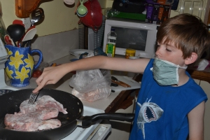 Mister cooking the chops with face mask on.