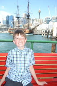 Mister in front of the Maritime Museum, Darling Harbour. You can see a Tall Ship in the background.