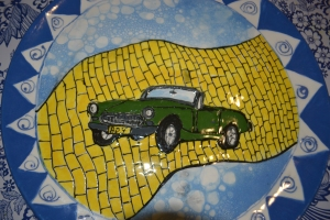 Geoff used to drive an Austen Healy Sprite which now in storage. I created this ceramic paint of the Spite seemingly flying along the Yellow Brick Road for his birthday before we got married. You could say the rubber hit the road what with the mortgage, kids and my health issues.