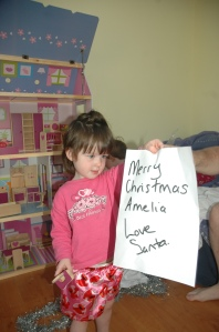 MIss with her doll's house. We had to qwrap it up in a big white sheet to wrap it up and tied tinsel around it.