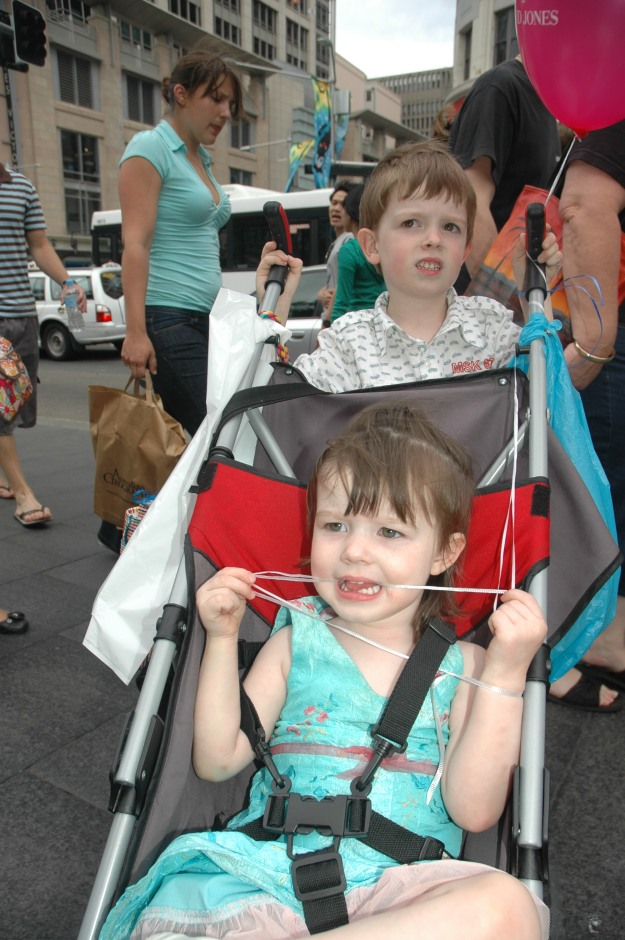 Mister pushing his little sister along George Street, Sydney 2008.