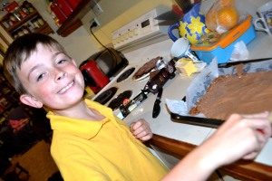 Mister spreading the melted chocolate topping over the base.