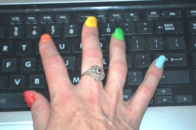 Tapping away with rainbow nails.