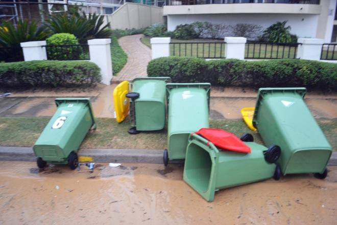 Rubbish bins thrown around beside the road.