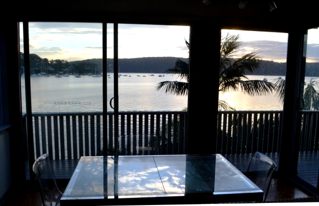 Sunseting over Pittwater with the cloudy sky reflected on the dining table.