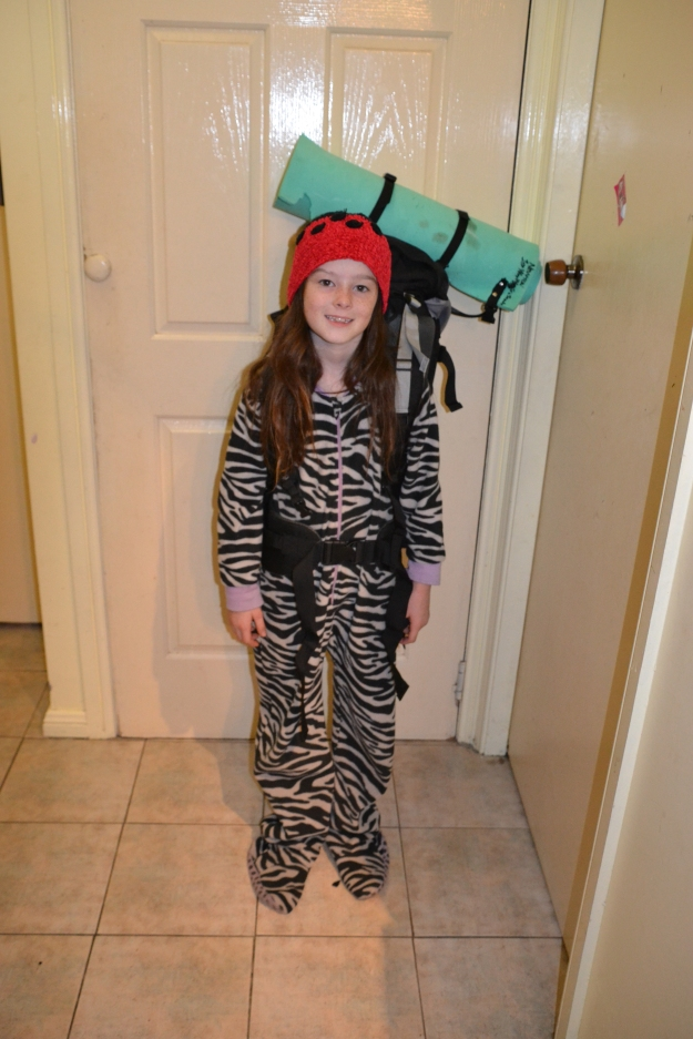 Miss trying out her pack in her zebra onesie the night before camp.