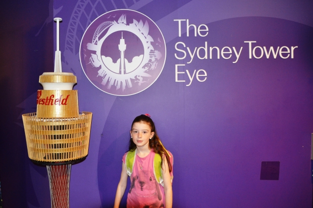 Miss standing next to a model of Sydney Tower.